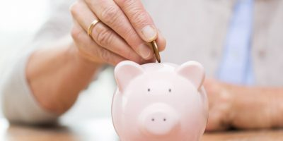 senior-woman-hand-putting-money-to-piggy-bank